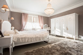 stock photo of enormous  - Enormous luxury old fashioned bedroom with crystal chandelier - JPG