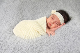 stock photo of girlie  - Newborn baby girl of Caucasian and Asian heritage wearing a lace head band - JPG