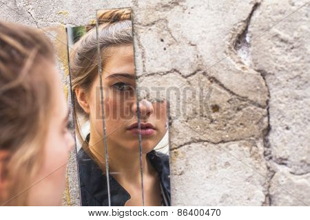 Teen girl looking at her reflection in the mirror fragments on the wall at street.