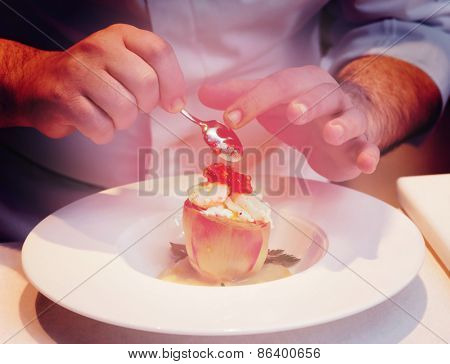 Chef is cooking a seafood appetizer, close-up, toned image
