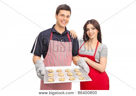 Young couple in aprons holding a pan with chocolate chip cookies and looking at the camera isolated on white background
