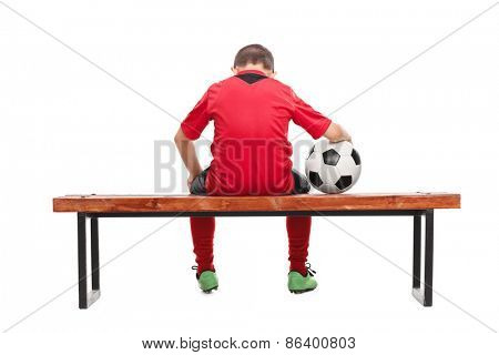 Rear view studio shot of a sad little boy in red soccer jersey seated on a bench and holding a ball isolated on white background