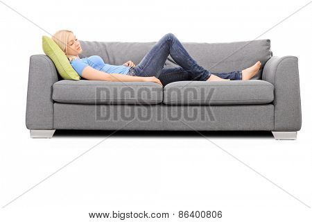 Studio shot of a young blond woman sleeping on a gray sofa isolated on white background