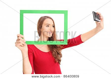 Studio shot of a beautiful girl taking a selfie with a cell phone, behind a green picture frame isolated on white background