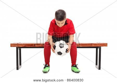 Worried little boy in red football shirt sitting on a bench and holding a ball isolated on white background