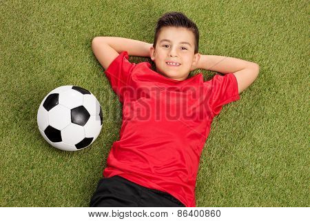 Carefree little boy in a red football jersey lying on grass with a ball next to him