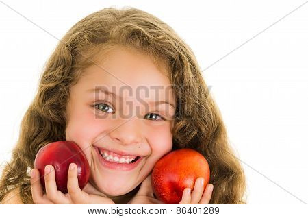Cute little preschooler girl holding two peaches