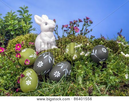 White Easter bunny sitting in the grass with painted easter eggs over blue sky
