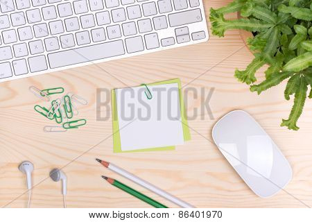 Desk with keyboard, notepaper and a cup of coffee, top view