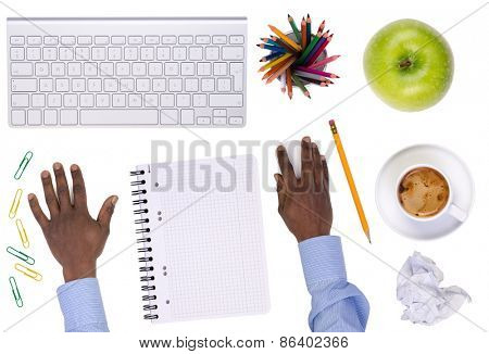 Office desktop with various objects and a businessman working, isolated on white