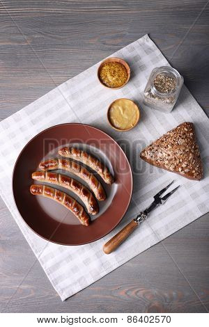 Grilled sausages on plate with bread on table close up