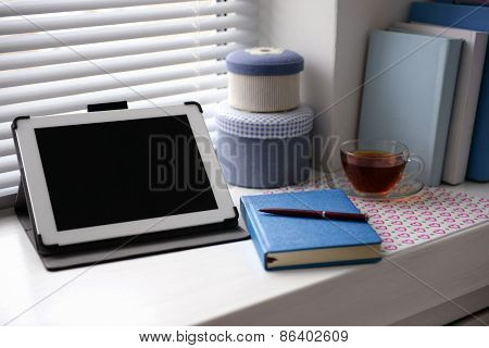 PC tablet, notebook and cup of tea on windowsill. Working place concept