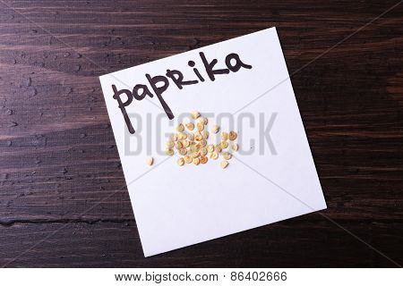 Paprika seeds on piece of paper on wooden background