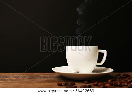 Cup of hot coffee with saucer on wooden table on black background