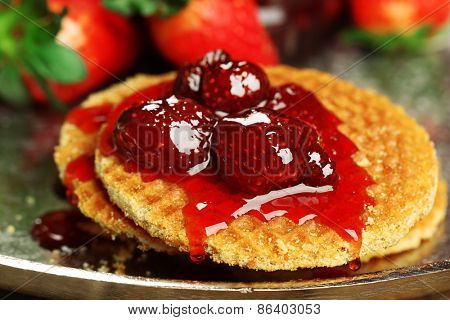Wafers with strawberry jam and berries on tray close up