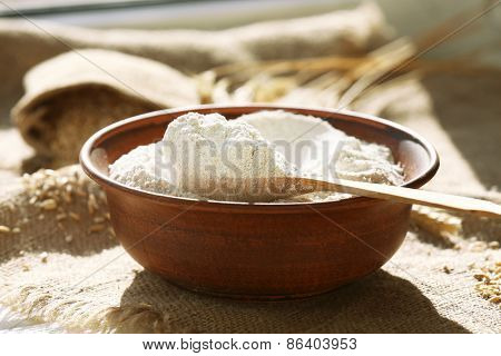 Bowl of flour with wooden spoon on burlap cloth background