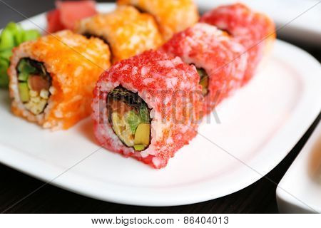 Sushi rolls on plate, soy sauce and chopsticks on wooden background