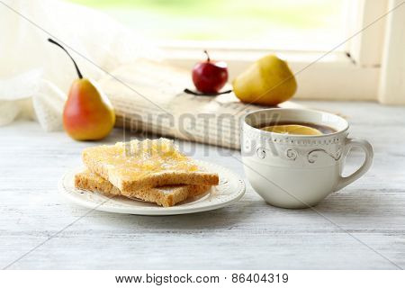 Toasts with honey on plate with cup of tea on light background