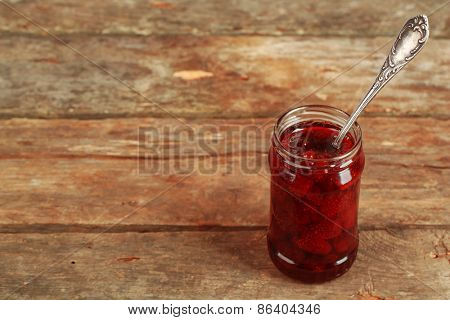 Jar of strawberry jam with spoon on wooden background