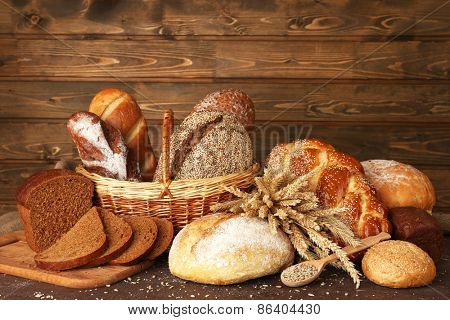 Different bread with ears and sunflower seeds on wooden background