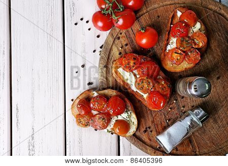 Slices of white toasted bread with butter and canned tomatoes on color wooden planks background