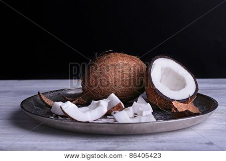 Cracked coconut on metal plate on color wooden table and dark background