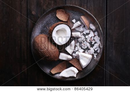 Cracked coconut on metal plate on rustic wooden table background