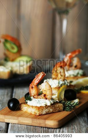 Appetizer canape with shrimp and olives on cutting board on table close up