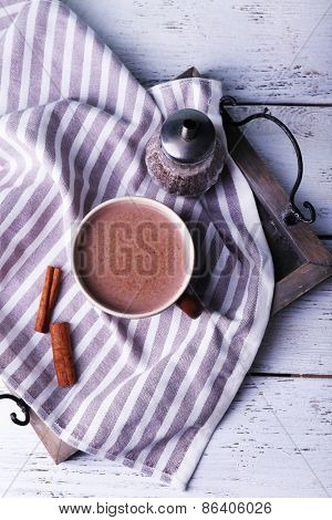 Cup of cocoa with cinnamon on tray and stripped napkin, closeup