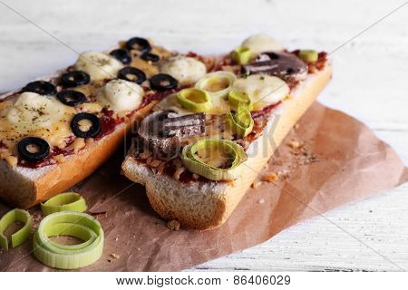 Tasty sandwich with vegetables and cheese on paper on wooden background