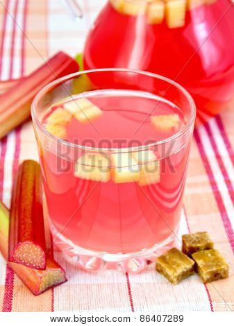 Compote from rhubarb in glassful and pitcher on linen tablecloth