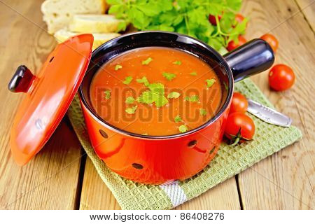 Soup tomato in red ware on board