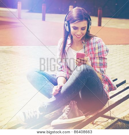 Happy teenage girl with smart phone and headphones in park