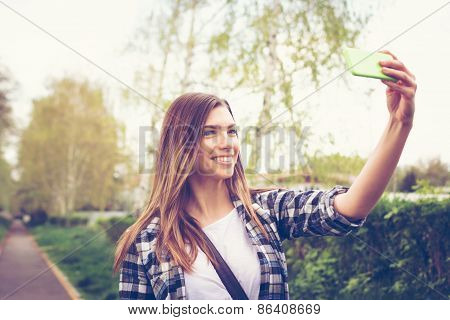 Teenage girl taking a selfie in park in spring