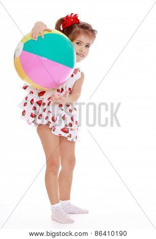 Girl in summer dress with a bouncy ball