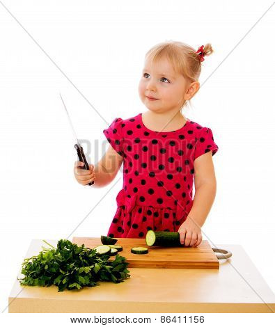 Little girl cuts a cucumber.
