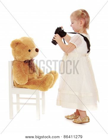 Little girl photographs on the camera teddy bear.