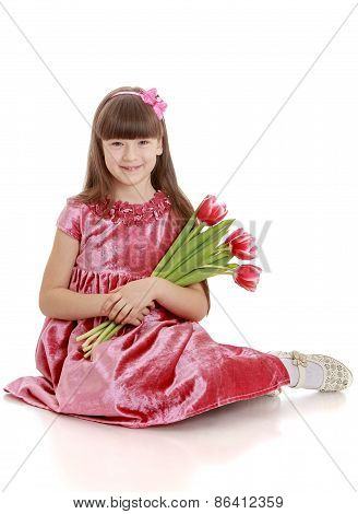The girl in elegant dress with a bouquet of tulips