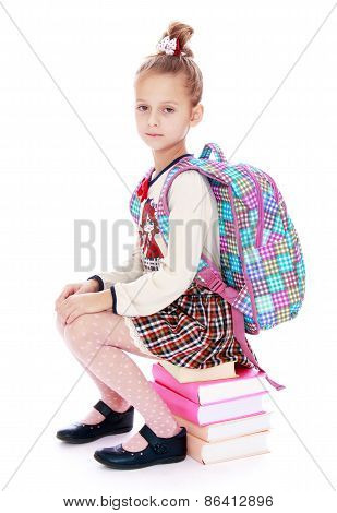 Schoolgirl with a backpack sitting on the books