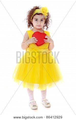 Girl in yellow dress holding red heart
