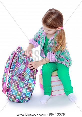 The girl opens a school backpack