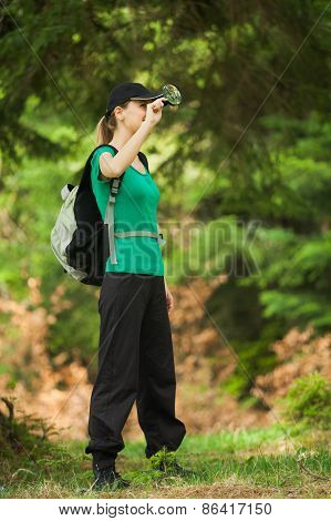 Hiker looking through loupe in forest
