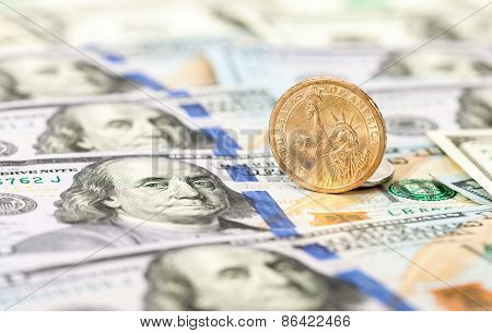 One American Dollar Coin Lying On Top Of One Hundred Dollar Bills Close Up