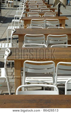 Row Of Empty Tables And Chairs