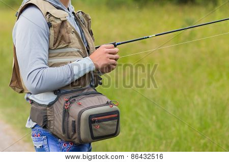 Fisherman holding spinning on the river bank