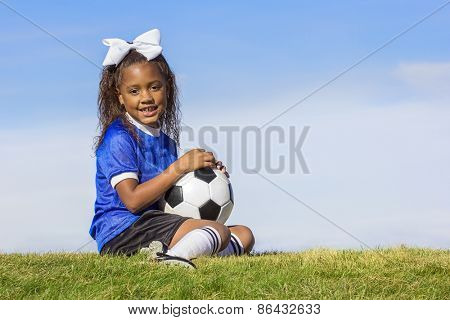 Cute, young african american girl soccer player holding a ball sitting on a grass field