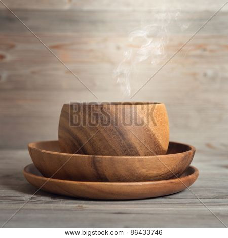 Empty bowl with hot steams on old wooden table. Dramatic light.