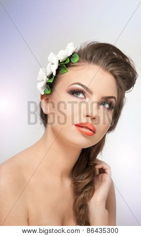 Portrait of beautiful girl in studio with white flowers arrangement in her hair and naked shoulders