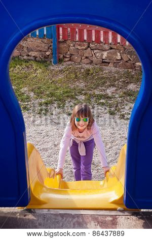 Girl In Sunglasses Plays On The Playground - Slide.