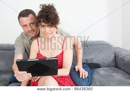 Delighted Couple Using A Tablet Computer In Their Living Room